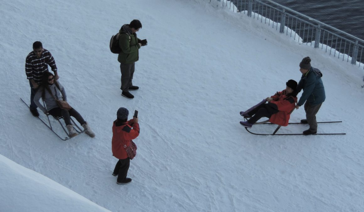 Glade kinesere leker seg med spark og fotografering i Kirkenes. Foto: Knut Anders Andersen.