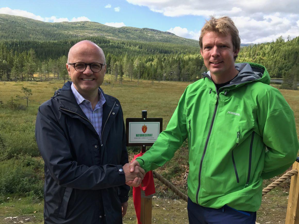 Klima- og miljøminister Vidar Helgesen og grunneier Ole Erik Elsrud gratulerer hverandre med en vellykket, frivillig verneprosess.