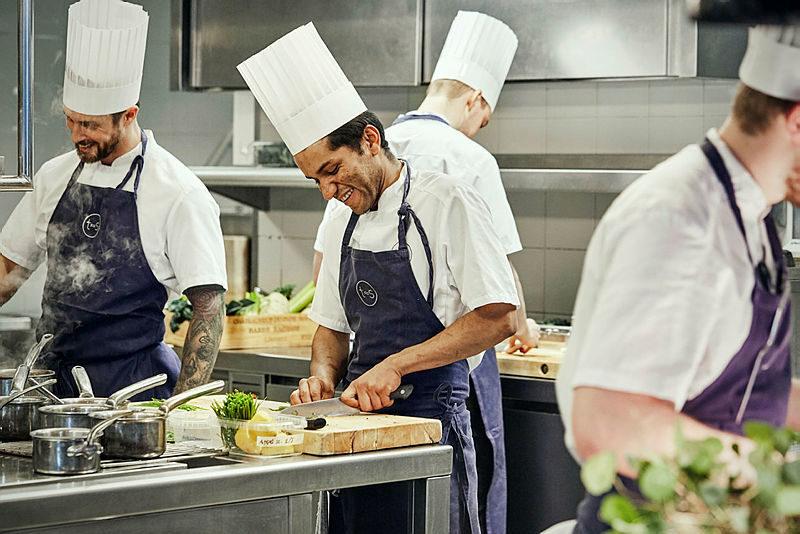Blide kokker i full sving på Tjuvholmen Sjømagasin i Oslo.